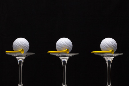 Three glasses of champagne with golf balls