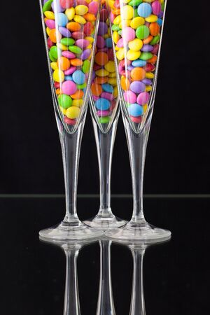 smarties: Color chocolate smarties inside the champagne glasses on a black glass plate Stock Photo