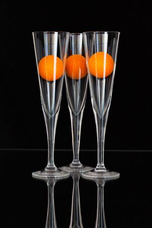 Three glasses of champagne with  orange golf balls on the glass plate photo