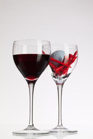 Wine glasses with red wine and golf ball on white table