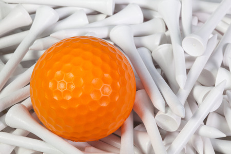 Orange golf ball lying between white wooden golf tees
