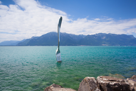 vevey: Vevey, Switzerland - July 8,2015: Giant steel fork in water of Geneva lake, Vevey, Switzerland.The fork went up in 1995 to mark the 10th anniversary of the Alimentarium, Veveys Food Museum.