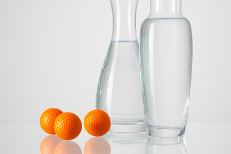 clean home: Two vases with clean water and golf balls on a glass table