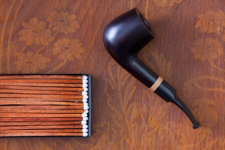 Luxury tobacco pipe on wooden table Stock Photo