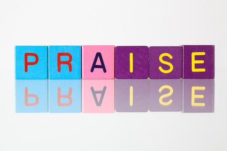 reverent: Praise - an inscription from childrens wooden blocks