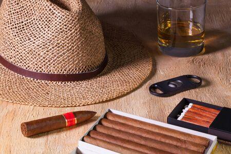 Siesta - cigarros, sombrero de paja y el whisky escocés en una mesa de madera
