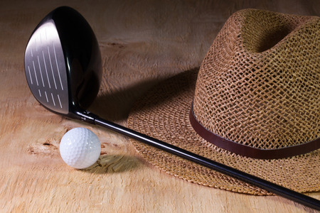 straw the hat: Siesta - straw hat and golf driver on a wooden table Stock Photo