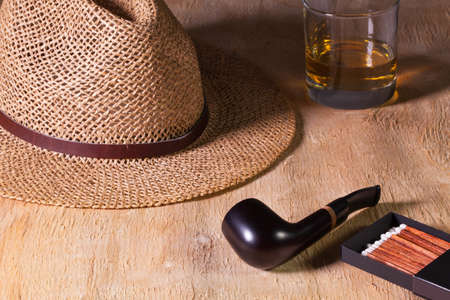 pipe dream: Siesta - pipe, straw hat and Scotch whiskey on a wooden table