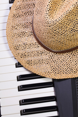 straw the hat: Detail of piano keyboard and straw hat