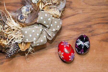 dry grass: Easter wreath with dry grass,pine cones, feathers, quail and Easter eggs on the wooden table Stock Photo