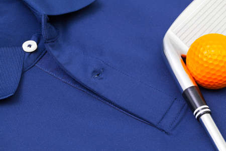 leisure wear: Detail of blue polo shirt and golf equipments