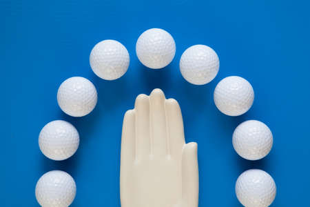 hand lay: Detail of ceramic hand with golf balls on the blue wooden desk - Flat Lay Photography Stock Photo