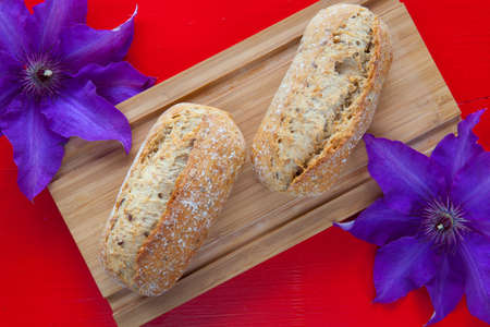 clematis flower: Fragrant breakfast - Two wheat bread and clematis flower on wooden desk