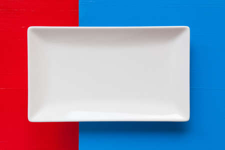 clean dishes: Empty white ceramic dish on over blue and red background, rectangle dish