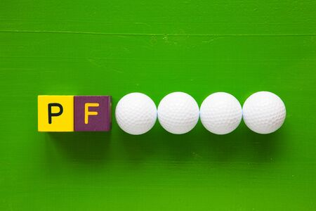 pour feliciter: P.F. - an inscription from childrens wooden blocks and golf ball - Flat Lay Photography