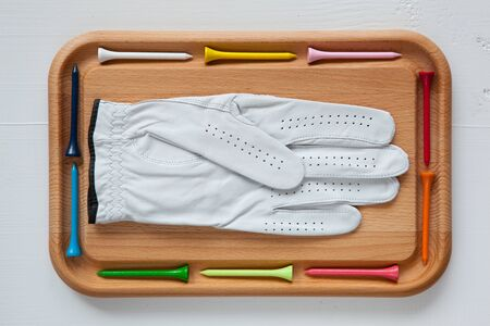 white glove: Cutting board with different wooden golf tees and white glove Stock Photo