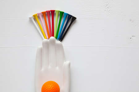 hand lay: Detail of ceramic hand with golf balls and tees on the white wooden desk - Flat Lay Photography Stock Photo