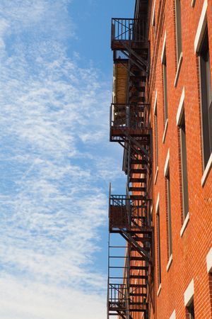 emergency stair: The typical american fire escape ladder zigzagging across the face and windows.Portland, USA