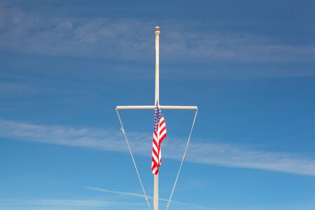 flagpole: American flag waving in the wind on the typical American flagpole before a blue sky