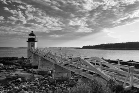 rocky point: Marshall Point Light as seen from the rocky coast of Port Clyde, Maine. Stock Photo