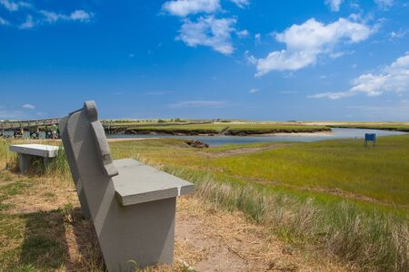 Concrete bench near the walkway to the dunes. Wooden walkway extends over marshland toward the distant dunes and ocean In Sandwich, Cape Cod, Massachusetts, USA