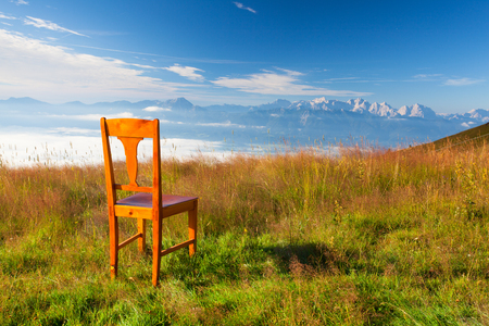 inversion: Old wooden chair on the top in Gerlitzen Apls in Austria.Inverse weather and view of the mountains in Slovenia. Stock Photo