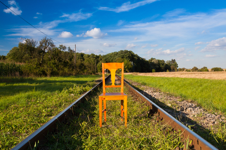 Railroad tracks and old wooden chair at sunset Stock Photo