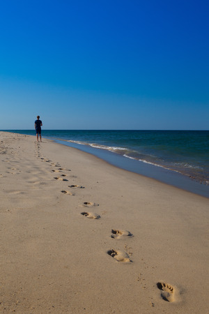 Man walking on the beach leaving footprints. Cape Cod, Massachusetts, USA