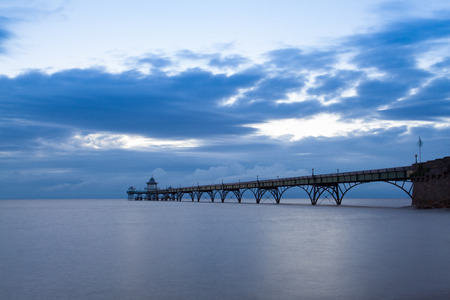 Long exposure landscape image of sea and pier with the soft light at sunset, Clevedon, Somerset, England, UK Stock Photo