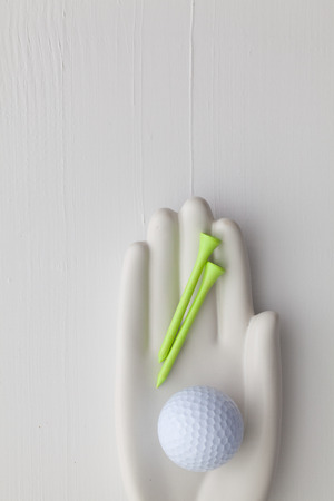 artifical: Detail of artifical hand with golf equipments  - Flat Lay Photography
