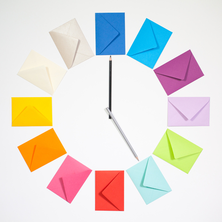 Twelve envelopes isolated on white background. Clock of colored envelopes for Christmas mailing. Stock Photo