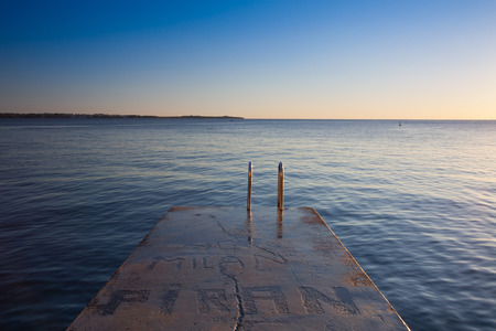 Lonely concrete dock of a city beach at sunset, Piran, Slovenia