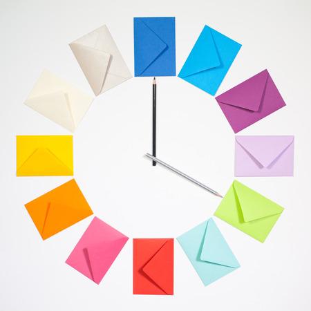 mailing: Twelve envelopes isolated on white background. Clock of colored envelopes for Christmas mailing. Stock Photo