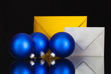 Gold and silver  envelopes and Christmas decoration on the black glass table