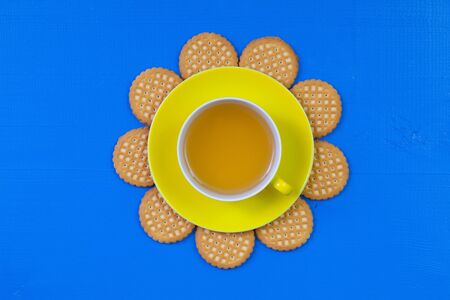 herbaceous: Funny arrangement  cup of tea on blue wooden table with sweet cookies - Flat lay image
