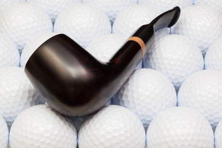 Luxury tobacco pipe on the white golf balls