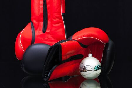 Red and black boxing gloves and Christmas decoration on black glass table. Christmas is not a struggle for Christmas gifts. Stock Photo