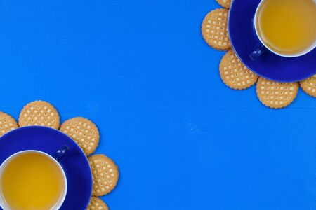 Funny arrangement  cups of tea on blue wooden table with sweet cookies - Flat lay image