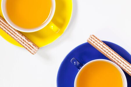 Perfect cups of tea on wooden table with sweet wafers - Flat lay image
