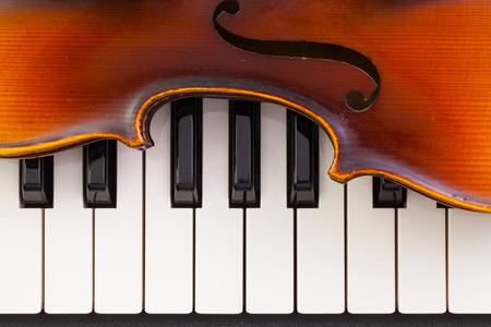 Très vieux violon couché sur le piano Banque d'images - 67055912