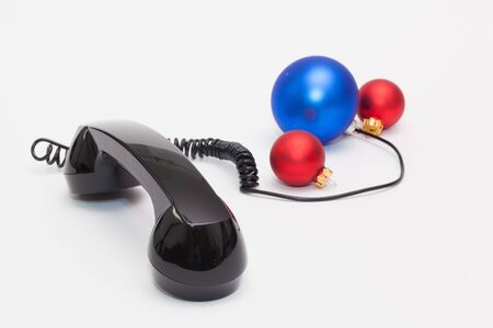 Old phone reciever and cord connection with Christmas decoration. Christmas hotline concept. Stock Photo