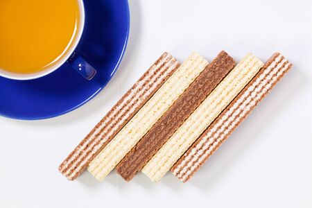 Perfect cup of tea on wooden table with sweet wafers - Flat lay image