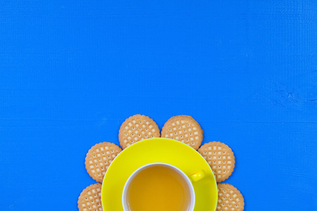 Funny arrangement  cup of tea on blue wooden table with sweet cookies - Flat lay image