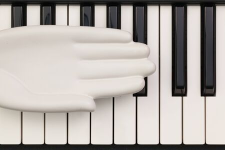 acoustically: Detail of ceramic hand on the piano keybords. Stock Photo