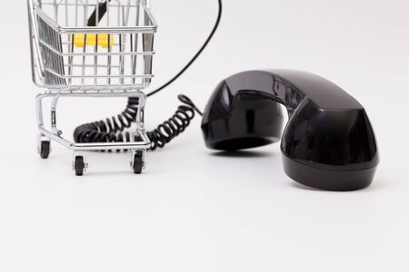 reciever: Old phone reciever and cord connection with shopping trolley. Shopping hotline concept.