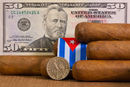 us coin: Luxury Cuban cigars with US dollar banknote and coin on the wooden table.