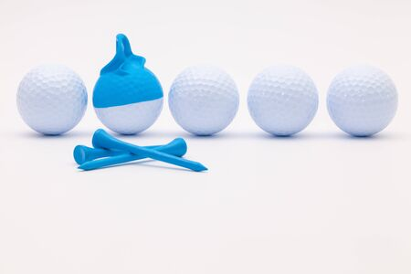 White golf balls with funny cap on the white background. Funny golf concept. Stock Photo