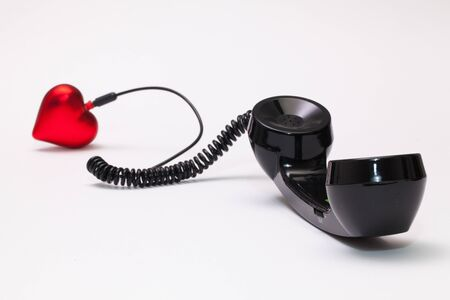 reciever: Old phone reciever and cord connection with red heart. Love hotline concept.