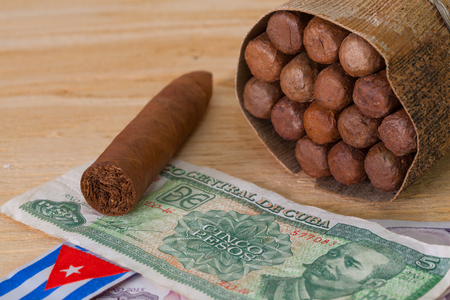 Luxury Cuban cigars and money on the wooden table Stock Photo