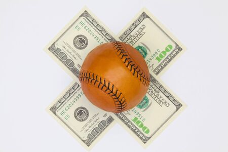 Leather baseball ball and us dollar banknotes on the white table. Flat lay photography